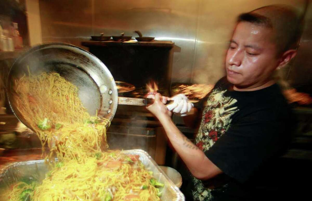 In this Sept. 3, 2011 photo, Israel Hernandez prepares food at the Bamboo Grove Hawaiian Grille, in Portland, Ore. Service firms grew at slightly faster pace in August compared to July, but the sector remains weak. (AP Photo/Rick Bowmer)