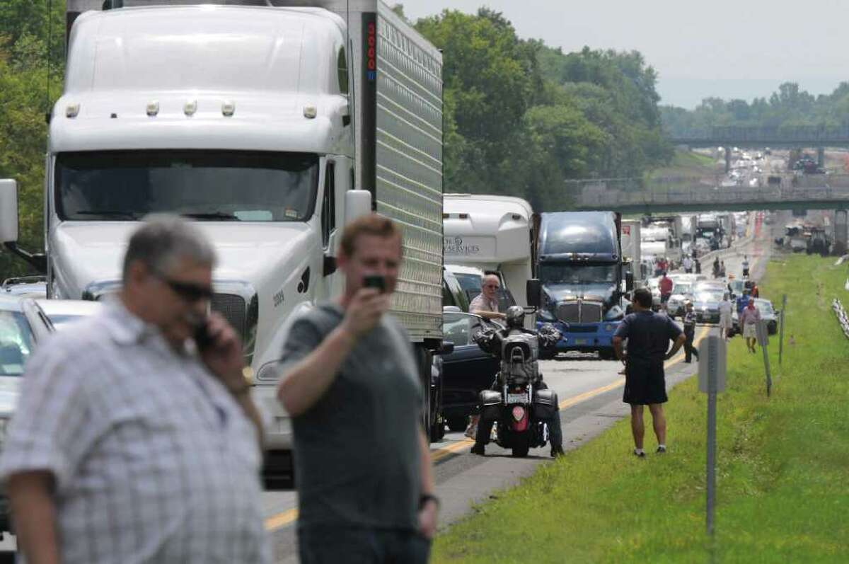 Drivers mill about outside of their vehicles, as traffic on the Thruway is stopped due to a gas line break between exits 23 and 24 on Wednesday Aug. 10, 2011 in Guilderland, NY. Traffic was eventually routed east across the median through a newly cut guardrail. (Philip Kamrass / Times Union)