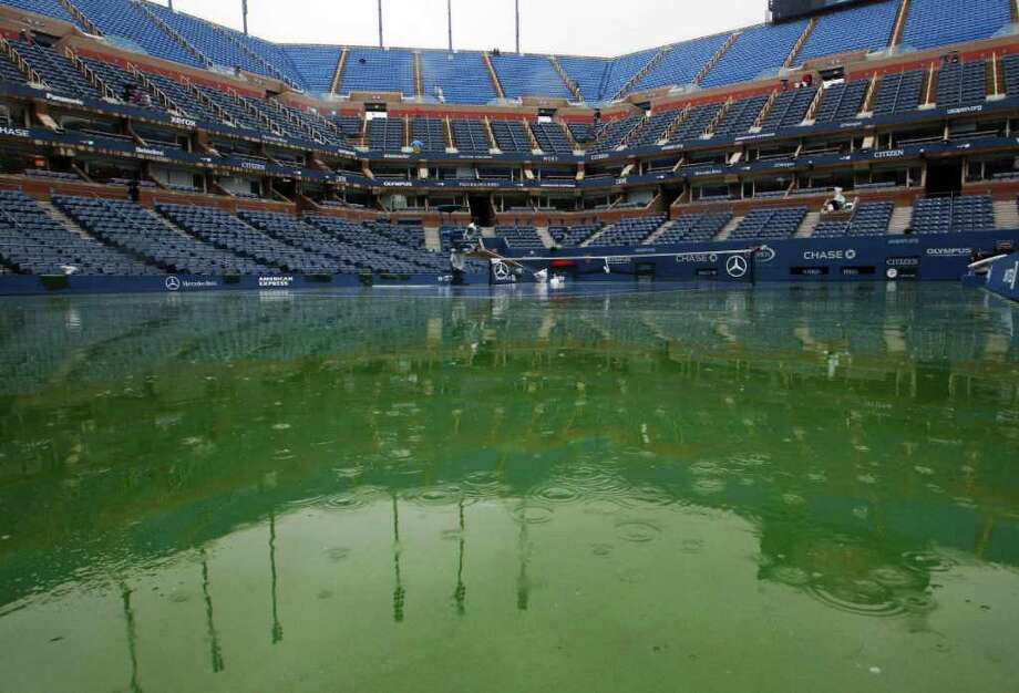 Water gathers on the court at Arthur Ashe Stadium during the U.S. Open tennis tournament in New York, Tuesday, Sept. 6, 2011. The start of play at the U.S. Open is being delayed because of rain. (AP Photo/Mel Evans) Photo: Mel Evans