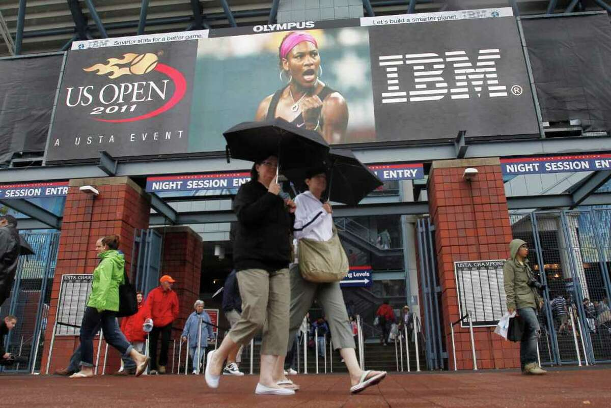 Fans walk near an entrance to Arthur Ashe Stadium during the U.S. Open tennis tournament in New York, Tuesday, Sept. 6, 2011. The U.S. Tennis Association announced just after 1:30 p.m. that because of unfavorable forecasts, it would have to cancel both the day and night sessions, hoping to resume play at 11 a.m. Wednesday, Sept. 7, 2011. (AP Photo/Mike Groll)