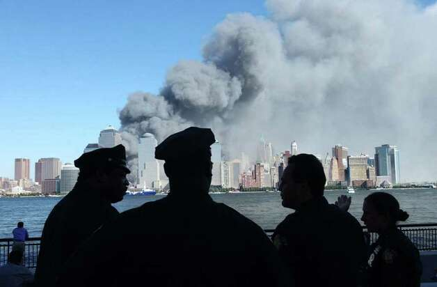 Times Union photo by STEVE JACOBS 9/11/01, New York, NY--  WATCHING THE ATTACK --  Jersey City Police officers watch the burning  World Trade Center buildings after an air attack Tuesday September 11,2001 ( for story Photo: STEVE JACOBSS / TIMES UNION