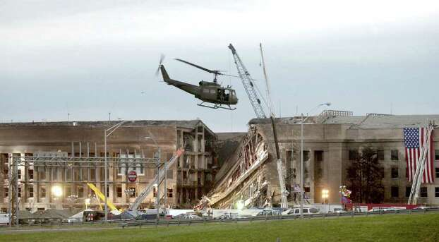 ARLINGTON, VA - SEPTEMBER 14, 2001:  A military helicopter flies in front of the Pentagon at the impact site where a hijacked airliner crashed into the building September 14, 2001 in Arlington, Virginia. This September 11 marks ten years since members of Al Qaeda hijacked four planes, attacking the World Trade Center and the Pentagon and crashing one in Shanksville, Pennsylvania, killing nearly 3,000 people in all. The effects continue to resonate across the global political landscape, as the United States concluded a nearly decade-long search for Al Qaeda leader Osama bin Laden, killing him in May 2011, and struggles to wind down two wars in Afghanistan and Iraq.  (Photo by Stephen J. Boitano/Getty Images) Photo: Stephen J. Boitano