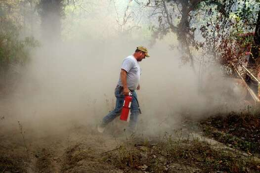 Curtis Heath uses a handheld fire extinguisher to spray hot spots on Henry Knight's property near Linden, Texas, Tuesday, Sept. 6, 2011, after a rekindle that caught a pile of tires on fire. Photo: AP