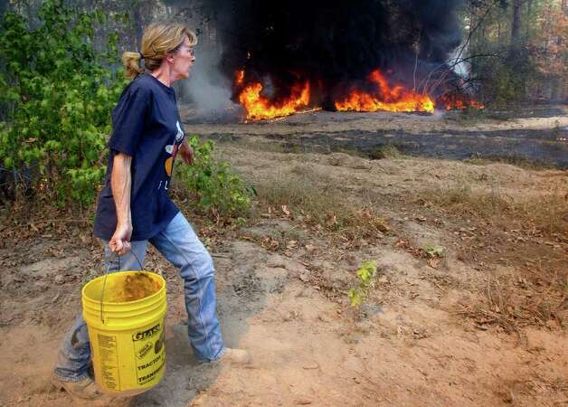 Tammy Heath carries a bucket of water Tuesday, Sept to be used in an attempt to keep fire from jumping a fire break at Henry Knight's home on Cass County Road 1614 near Linden, Texas. Heath, her husband, and son helped keep the fire from destroying the Knights' home and several out buildings. Photo: AP