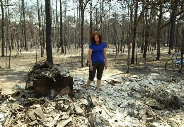 Deborah Torkelson looks at what's left of her home on Tuesday Sept. 6, 2011, that was destroyed by fire in Bastrop, Texas.   More than 1,000 homes have been destroyed in at least 57 wildfires across rain-starved Texas, most of them in one devastating blaze near Austin that is still raging out of control, officials said Tuesday.  (AP Photo/Austin American-Statesman, Jay Janner)  MAGS OUT; NO SALES; TV OUT; INTERNET OUT; AP MEMBERS ONLY Photo: AP