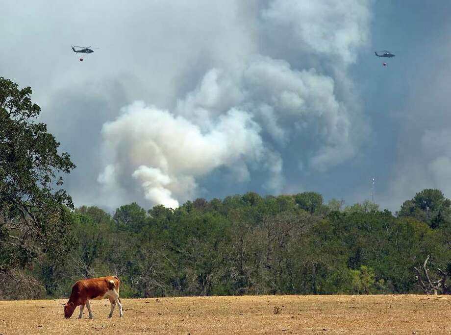 A fire flares up a along Highway 21 near Highway 95 on Tuesday, Sept. 6, 2011 in Bastrop, Texas.  More than 1,000 homes have been destroyed in at least 57 wildfires across rain-starved Texas, most of them in one devastating blaze near Austin that is still raging out of control, officials said Tuesday.  (AP Photo/Austin American-Statesman, Ralph Barrera)  MAGS OUT; NO SALES; TV OUT; INTERNET OUT; AP MEMBERS ONLY Photo: AP