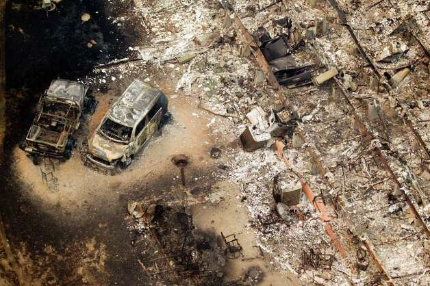 In this aerial photo,  burned out house and cars are seen on Tuesday, Sept. 6, 2011, near Magnolia, Texas.  More than 1,000 homes have been destroyed in at least 57 wildfires across rain-starved Texas, most of them in one devastating blaze near Austin that is still raging out of control, officials said Tuesday. Photo: AP