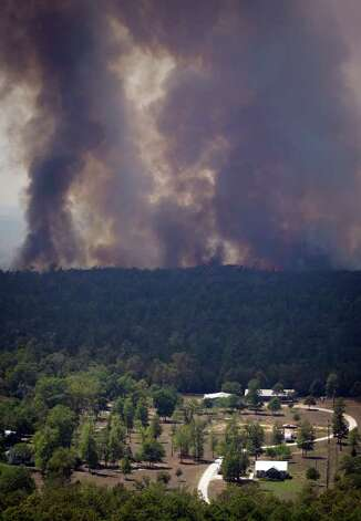 A wildfire burns in the forest behind homes near Magnolia, Texas.  More than 1,000 homes have been destroyed in at least 57 wildfires across rain-starved Texas, most of them in one devastating blaze near Austin that is still raging out of control, officials said Tuesday. Photo: AP
