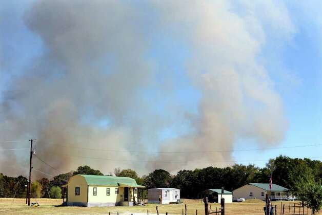 Smoke rises up from a fire slowly moving towards a home   near Rugby, Texas Tuesday, Sept. 6, 2011. Photo: AP