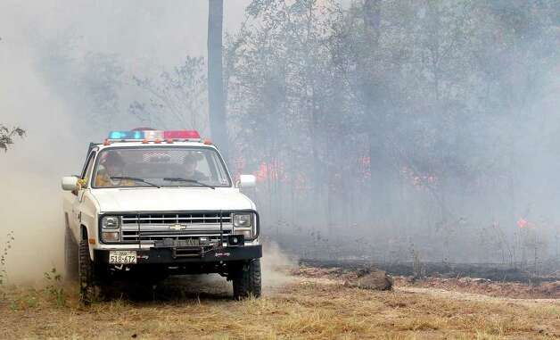 Volunteer firefighters retreat back Texas Farm-to-Market Road 196 Tuesday, Sept. 6, 2011 while fighting a massive grass fire near Rugby, Texas. Photo: AP