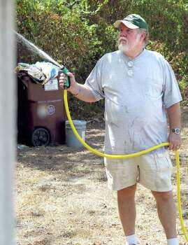 Donnie Bazhaw waters down a tool shed at his home Tuesday, Sept. 6, 2011 in Paris, Texas. Photo: AP