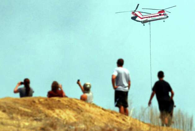 People on a hillside watch a helicopter drop water on wildfires east of Bastrop, Texas Tuesday September 6, 2011. JOHN DAVENPORT/jdavenport@express-news.net Photo: SAN ANTONIO EXPRESS-NEWS