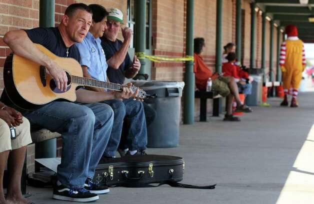 Pat McGuire (left) plays his guitar at Bastrop Middle School where hundreds of people have come to receive aid after wildfires swept through the area. McGuire, a volunteer, said he just hoped to brighten somebody's day. (Tuesday September 6, 2011) JOHN DAVENPORT/jdavenport@express-news.net Photo: SAN ANTONIO EXPRESS-NEWS