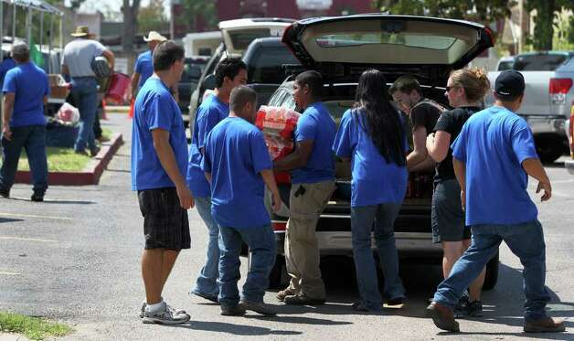 Volunteers at Ascension Catholic Church remove donated goods from a car Tueday September 6, 2011 where those affected by central Texas wildfires can receive aid. JOHN DAVENPORT/jdavenport@express-news.net Photo: SAN ANTONIO EXPRESS-NEWS