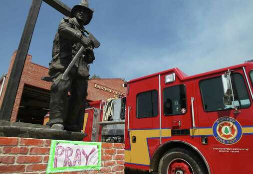 A sign at the base of a fireman's statue at the Bastrop Fire Department encourages people to pray as wild fires has swept through the Bastrop area. (Tuesday September 6, 2011) JOHN DAVENPORT/jdavenport@express-news.net Photo: SAN ANTONIO EXPRESS-NEWS