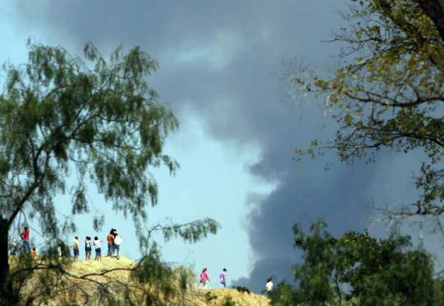 People on a hillside watch a helicopter drop water on wildfires east of Bastrop, Texas Tuesday September 6, 2011. JOHN DAVENPORT/jdavenport@express-news.net Photo: JOHN DAVENPORT, SAN ANTONIO EXPRESS-NEWS / SAN ANTONIO EXPRESS-NEWS