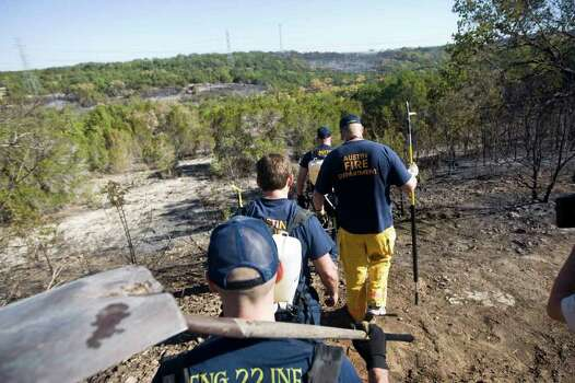 Austin Fire fighters make their way to check on hot spots in the Steiner Ranch residential area on Tuesday, Sept. 6, 2011 outside Austin, Texas.   More than 1,000 homes have been destroyed in at least 57 wildfires across rain-starved Texas, most of them in one devastating blaze near Austin that is still raging out of control, officials said Tuesday.  (AP Photo/Austin American-Statesman, Ricardo B. Brazziell)  MAGS OUT; NO SALES; TV OUT; INTERNET OUT; AP MEMBERS ONLY Photo: AP