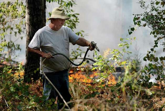 A volunteer directs a hose normally used to apply chemicals in his lawn care business at a portion of a massive wildfire which has reported burned more than 2,600 acres near Lilbert, Texas, on Tuesday, Sept. 6, 2011. The man, who requesed his name not be used, said he heard about the fire and volunteered his sprayer truck to help battle the blaze. (AP Photo/The Daily Sentinel, Andrew D. Brosig) MANDATORY CREDIT Photo: AP