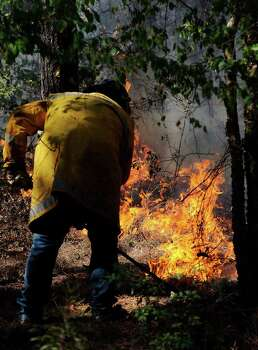 A volunteer firefighter uses a rake to extinguish flames on the front lines of a massive wildfire near Lilbert, Texas, on Tuesday, Sept. 6, 2011. The Texas Forest Service reported the fire, which started Sept. 4, 2011, had consumed more than 2,600 acres as crews continued to battle the blaze. (AP Photo/The Daily Sentinel, Andrew D. Brosig) MANDATORY CREDIT Photo: AP
