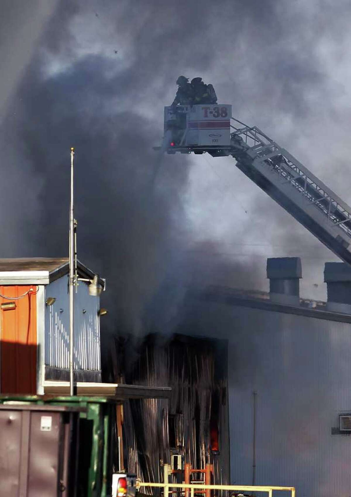 Firefighters fight a blaze at a warehouse near the intersection of Loop 410 and Perrin Beitel Road near the airport on Tuesday, Sept. 6, 2011. The intersection and several blocks were evacuated due to fumes emitted from the fire. Over 30 units were called to the scene to work the fire. Kin Man Hui/kmhui@express-news.net