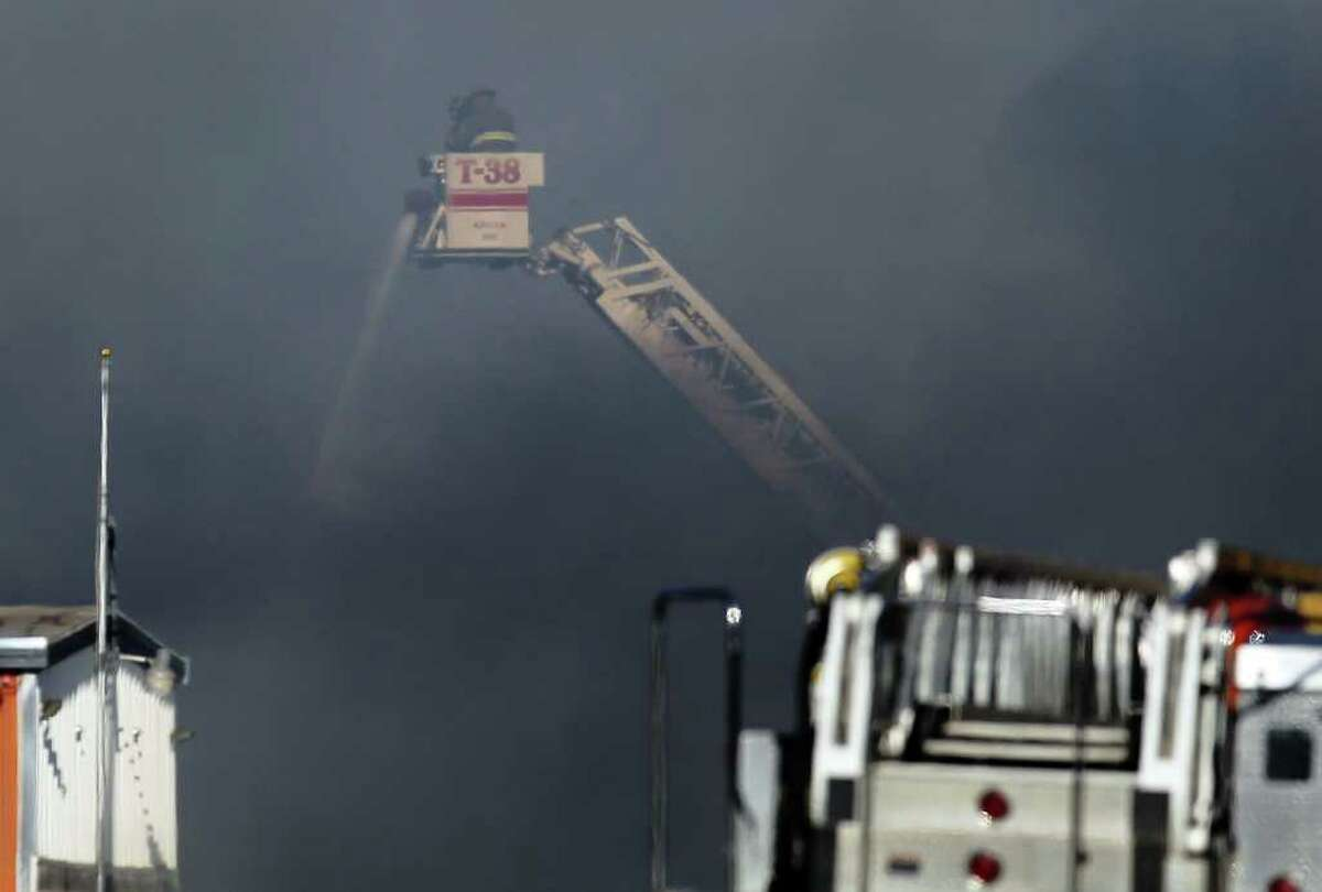 Smoke nearly engulfs a pair of firefighters working a warehouse fire at the intersection of Loop 410 and Perrin Beitel near the airport on Tuesday, Sept. 6, 2011. The intersection and surrounding area was evacuated due to concerns from the fumes emitted from the fire. Over 30 units were called out to battle the blaze. Kin Man Hui/kmhui@express-news.net