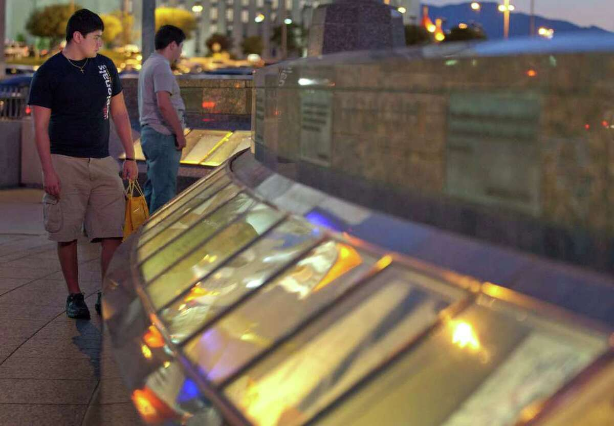 """In this June 22, 2011 photo, Victor, left, and Ben Ortega, brothers from El Paso, Texas, walk along the September 11 memorial outside the New York, New York Hotel and Casino, in Las Vegas. Across the country, an extravagant ritual of public grief for """"our losses"""" has not abated in a decade, from public memorials of steel and photos to the palpable sadness of strangers. Experts say Americans are still processing the most tragic public event of their lifetimes, before they can begin to let go. (AP Photo/Julie Jacobson)"""