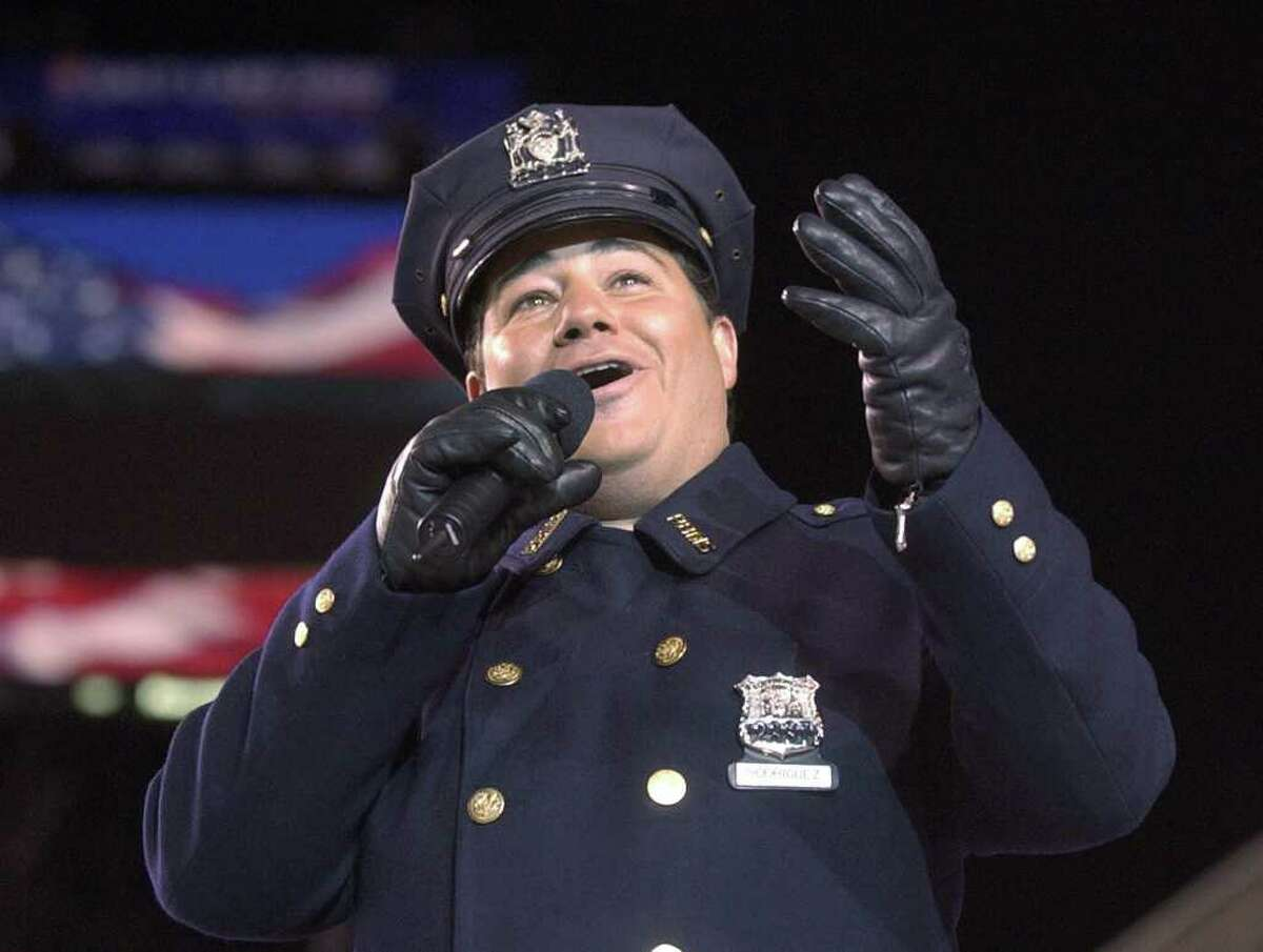 """New York City police officer Daniel Rodriguez sings """"God Bless America"""" during the pre-show activities before the opening ceremonies of the 2002 Winter Olympics in Salt Lake City Friday, Feb. 8, 2002. (AP Photo/Amy Sancetta)"""