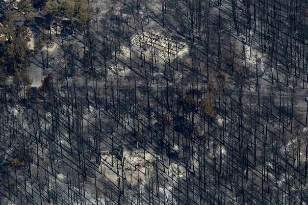 An area destroyed by wildfire is seen, Wednesday, Sept. 7, 2011, in Bastrop, Texas. The fire has destroyed more than 600 homes and blackened about 45 square miles in and around Bastrop. A search team on Wednesday will begin looking for more possible victims of the fire, which has killed two people and forced thousands to evacuate. Photo: AP