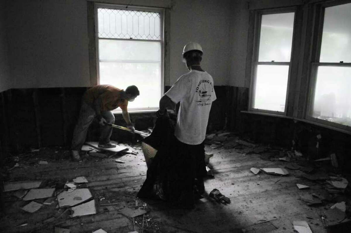 Contractors Anthony Corona, left, and Billy Westberry from Florida, work rehabbing a home that had been damaged by flood waters on Wednesday, Sept. 8, 2011 in Schoharie. Many in the community have evacuated again as the Schoharie Creek has risen out of its banks because of recent heavy rain. (Paul Buckowski / Times Union)