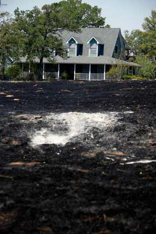 Fire damage is seen surrounding a home Wednesday Sept. 7, 2011 in the Alum Creek area east of Bastrop in the aftermath of the Bastrop County Complex wildfire that charred more than 33,000 acres.   (William Luther/wluther@express-news.net) Photo: WILLIAM LUTHER, SAN ANTONIO EXPRESS-NEWS / 2011 SAN ANTONIO EXPRESS-NEWS