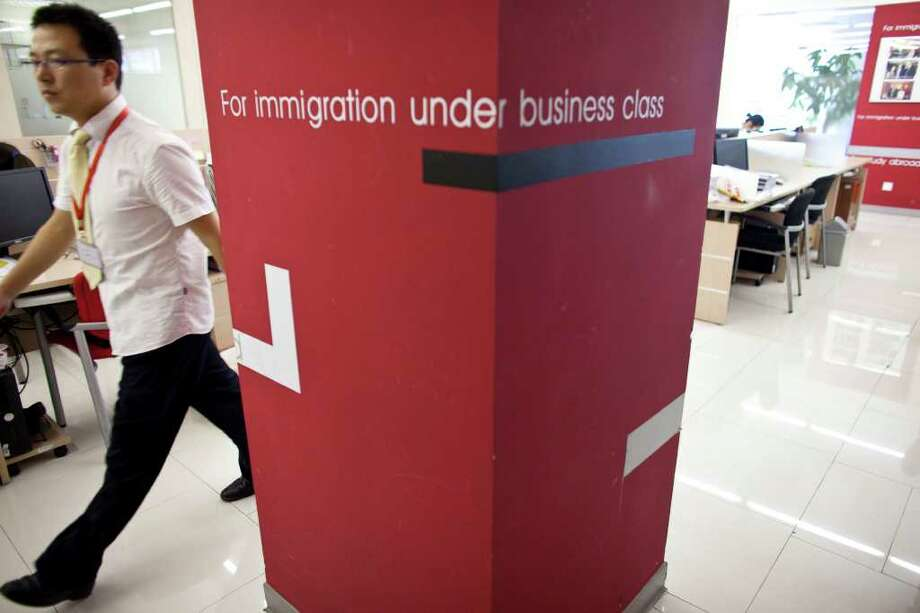 In this Aug. 1, 2011 photo, a worker walks inside an office of Beijing Goldlink Go-Abroad Consulting Co., an immigration consulting firm assisting Chinese to immigrate to Canada and the United States, in Beijing. Among the 20,000 Chinese with at least 100 million yuan ($15 million) in individual investment assets, 27 percent have already emigrated and 47 percent are considering it, according to a report by China Merchants Bank and U.S. consultants Bain & Co. published in April. (AP Photo/Alexander F. Yuan) Photo: Alexander F. Yuan, STF / AP