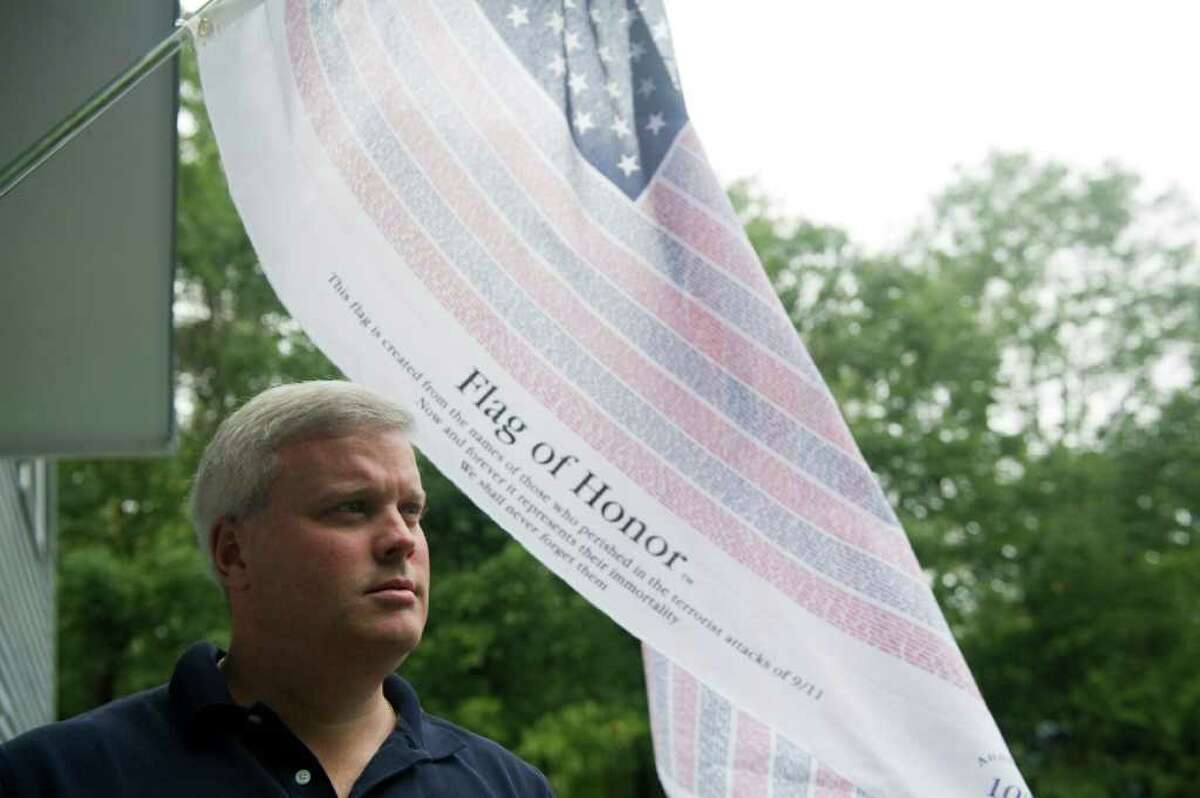 Christopher Murphy outside his home where a commemorative flag recognizing the 10th anniversary of 9-11 hangs in New Canaan, Conn., September 7, 2011. Murphy was working at 1 New York Plaza and wearing the same blue shirt her wears here on the morning of the Sept. 11, 2001. His cousin, James F. Murphy IV, who was 30 at the time, was in the Windows of the World restaurant the morning of the attack and was not able to get out of the building.