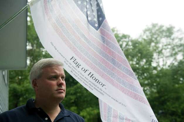 Christopher Murphy outside his home where a commemorative flag recognizing the 10th anniversary of 9-11 hangs in New Canaan, Conn., September 7, 2011. Murphy was working at 1 New York Plaza and wearing the same blue shirt her wears here on the morning of the Sept. 11, 2001. His cousin, James F. Murphy IV, who was 30 at the time, was in the Windows of the World restaurant the morning of the attack and was not able to get out of the building. Photo: Keelin Daly / Stamford Advocate