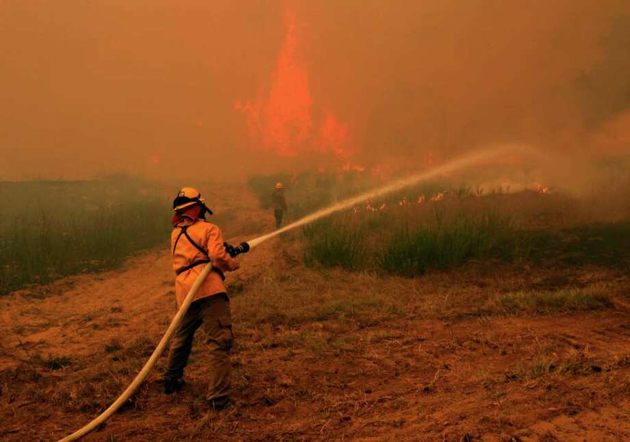 Firefighters from around the state battle a large wildfire on Highway 71 near Smithville, Texas, Monday, Sep. 5, 2011.  A roaring wildfire raced unchecked Monday through rain-starved farm and ranchland in Texas, destroying nearly 500 homes during a rapid advance fanned in part by howling winds from the remnants of Tropical Storm Lee.  (AP Photo/Erich Schlegel) Photo: Erich Schlegel, FRE / FR 62355 AP