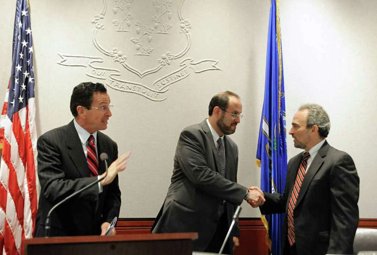 New State Department of Education Commissioner Stefan Pryor, center, shakes the hand of Chairman of the State Board of Education, Allan Taylor, right, as Gov. Dannel P. Malloy, left, waves, at the Legislative Office Building in Hartford, Conn., Wednesday, Sept. 7, 2011. (AP Photo/Jessica Hill)