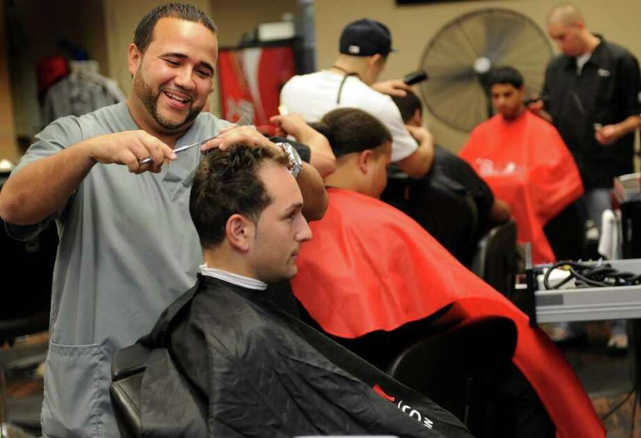Alex Martinez, owner of Al's Millenium Cuts, takes a little off the top for client Joey Lupone, of Derby, Wednesday, Sept. 7, 2011 at the shop at 4003 Main Street in Bridgeport, Conn.  The business used to be located in downtown Bridgeport but it was destroyed in last year's tornado. Photo: Autumn Driscoll / Connecticut Post