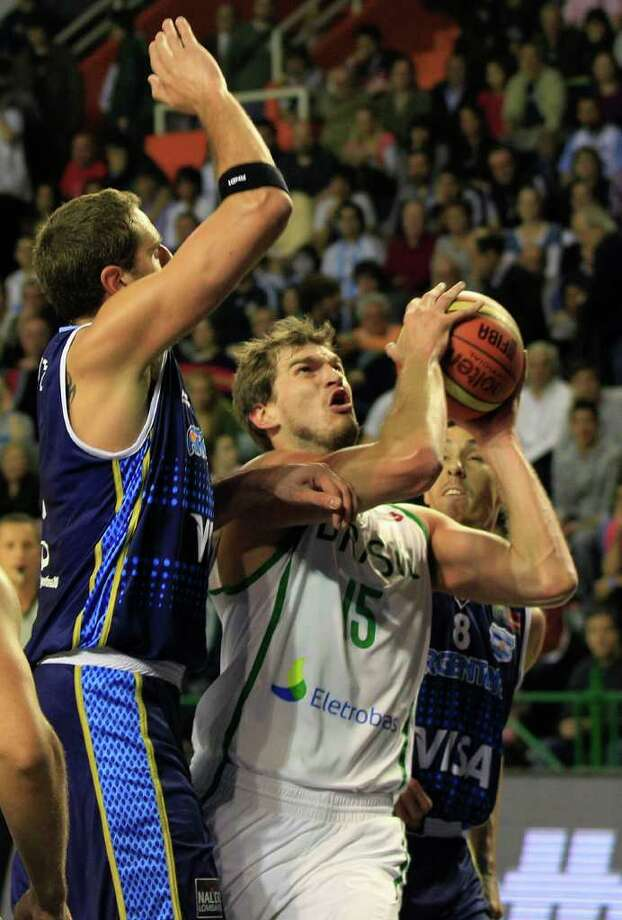Brazil's Tiago Splitter, right, goes up for a shot against Argentina's Juan Gutierrez during a FIBA Americas Championship basketball game in Mar del Plata, Argentina, Wednesday, Sept. 7, 2011. The top two finishers of the tournament get an automatic berth in the 2012 London Olympics and the next three advance to the last-chance Olympic qualifier to be held in July 2012. Photo: Martin Mejia/Associated Press