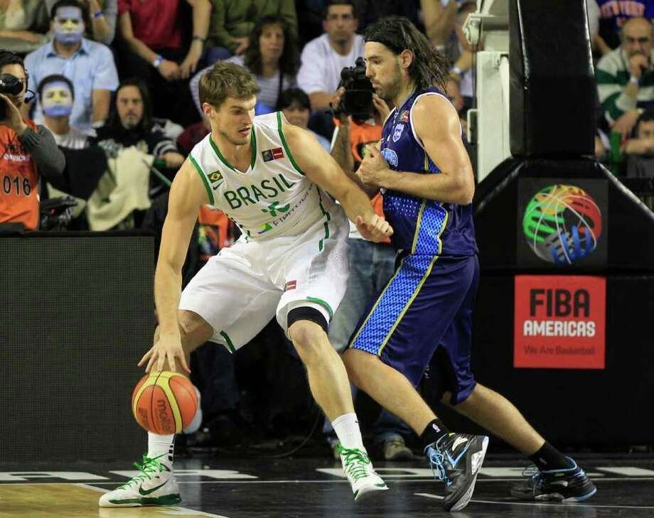 Brazil's Tiago Splitter, left, is challenged by Argentina's Luis Scola during a FIBA Americas Championship basketball game in Mar del Plata, Argentina, Wednesday, Sept. 7, 2011. The top two finishers of the tournament get an automatic berth in the 2012 London Olympics and the next three advance to the last-chance Olympic qualifier to be held in July 2012. Photo: Martin Mejia/Associated Press