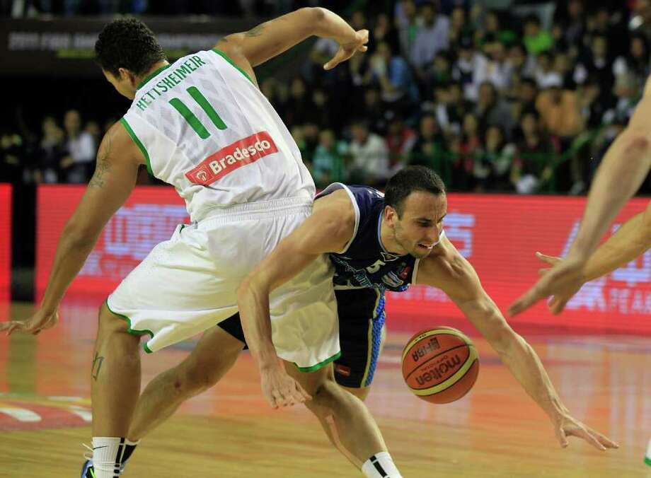 Argentina's Manu Ginobili, right, falls down after attempting to dribbles past Brazil's Rafael Hettsheimer during a FIBA Americas Championship basketball game against Brazil in Mar del Plata, Argentina, Wednesday, Sept. 7, 2011. The top two finishers of the tournament get an automatic berth in the 2012 London Olympics and the next three advance to the last-chance Olympic qualifier to be held in July 2012. Photo: Martin Mejia/Associated Press