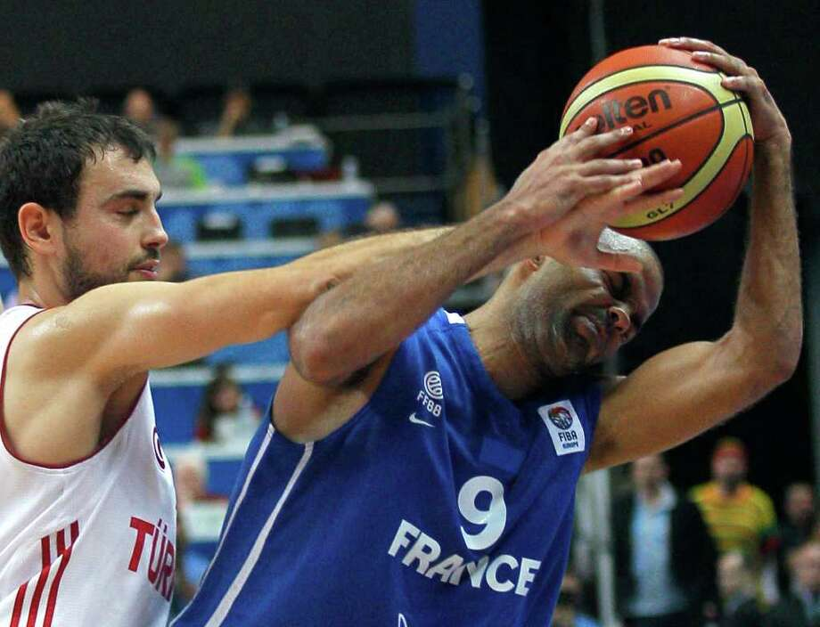 Turkey's Ender Arslan, left, challenges for the ball with France's Tony Parker during their EuroBasket European Basketball Championship Group E match in Vilnius, Lithuania, Wednesday Sept. 7, 2011. Photo: Darko Vojinovic/Associated Press / AP