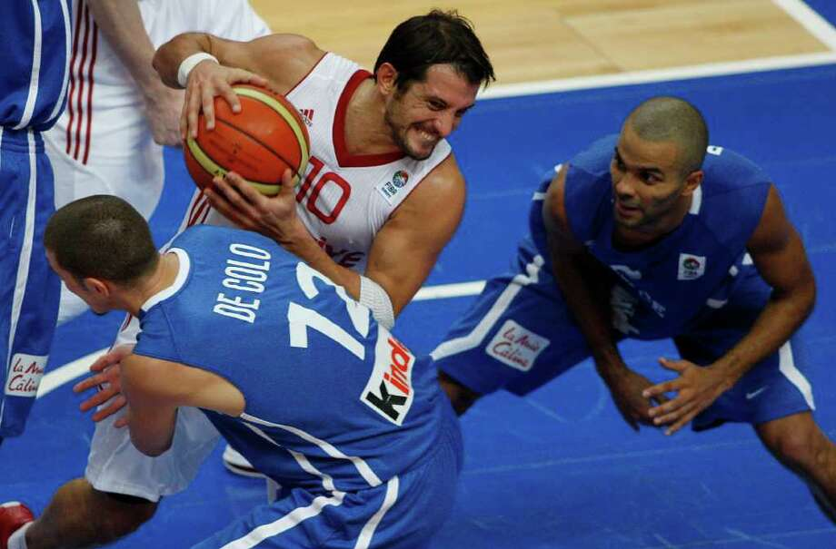 Tony Parker, right, and Nando De Colo, left, both from France challenges Kerem Tunceri, center, from Turkey during the EuroBasket European Basketball Championship Group E match in Vilnius, Lithuania, Wednesday, Sept. 7, 2011. France won the match 88-84. Photo: Petr David Josek/Associated Press / AP