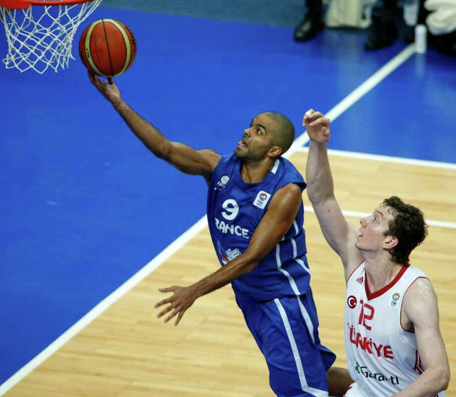 Tony Parker, left, from France shoots on basket past Omer Asik, right, from Turkey during the EuroBasket European Basketball Championship Group E match in Vilnius, Lithuania, Wednesday, Sept. 7, 2011. France won the match 88-84. Photo: Petr David Josek/Associated Press / AP