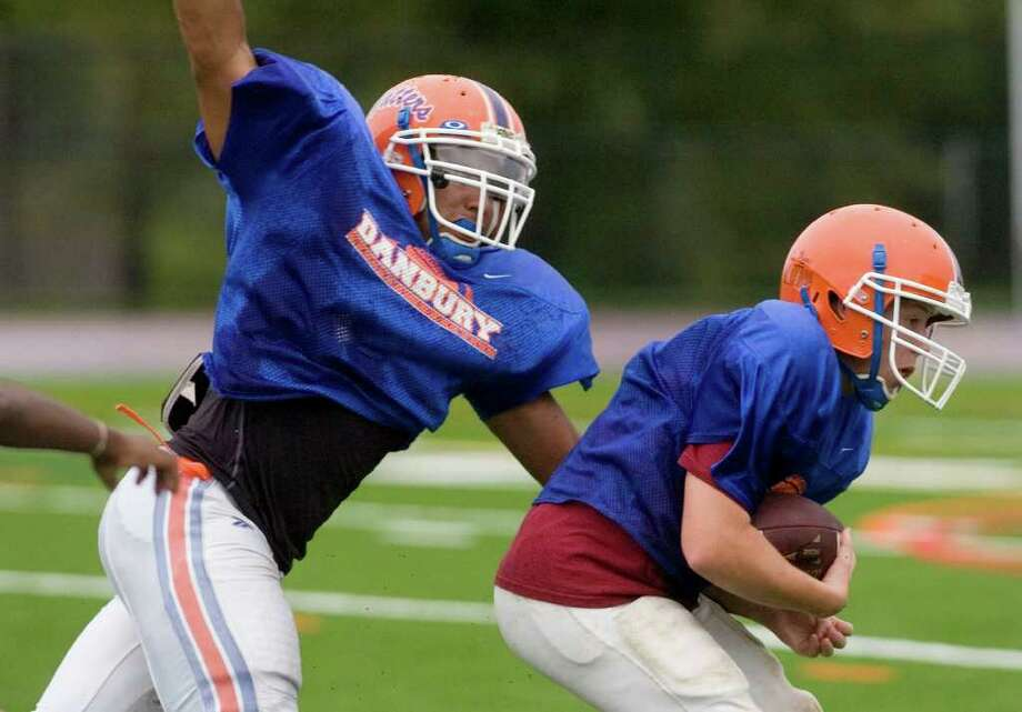 Austin Calitro, left, works on defense during practice at Danbury High School on Wednesday, Sept. 7, 2011. Photo: Jason Rearick / The News-Times