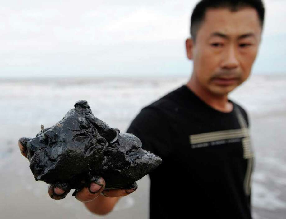 Chinese man holds up oil residue found in his shrimp farm in the coastal Leting county in the Bohai Bay.  Associated press / CHINATOPIX