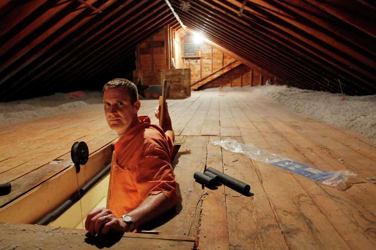 CORRECTS SPELLING OF NAME TO BOTELHO, NOT BOTEHLO - In this June 22, 2011 photo, Stephen Botelho stands in the entrance to his attic, at his Westwood, Mass., home. Botelho has installed cellulose insulation to the attic as an energy saving measure. (AP Photo/Steven Senne)