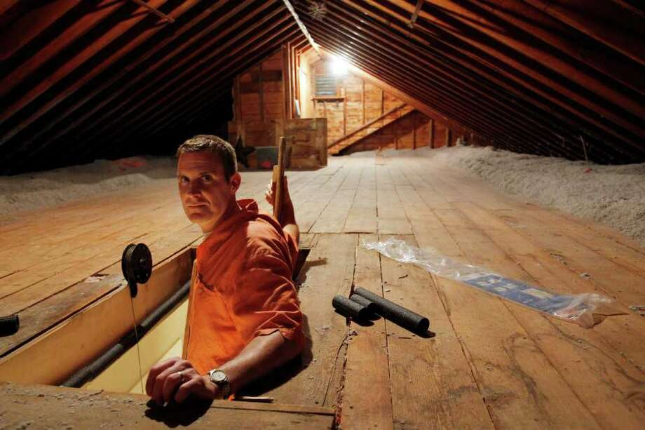 CORRECTS SPELLING OF NAME TO BOTELHO, NOT BOTEHLO - In this June 22, 2011 photo, Stephen Botelho stands in the entrance to his attic, at his Westwood, Mass., home. Botelho has installed cellulose insulation to the attic as an energy saving measure. (AP Photo/Steven Senne) Photo: Steven Senne