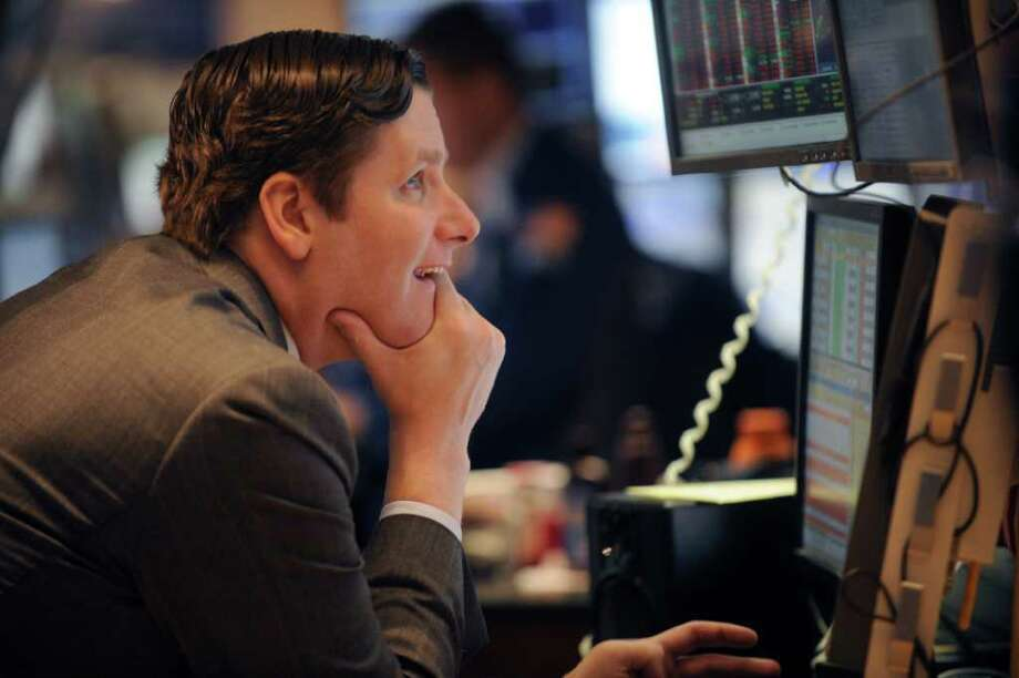In this Sept. 6, 2011 photo, Gregg Maloney of Barclays Capital, works on the floor of the New York Stock Exchange. Global stocks rebounded Wednesday, Sept. 7, from the previous day's steep sell-off as investor sentiment was buoyed by a German court decision backing the country's participation in European bailouts. The Swiss franc, meanwhile, hovered around the level it was pegged at. (AP Photo/Henny Ray Abrams) Photo: Henny Ray Abrams