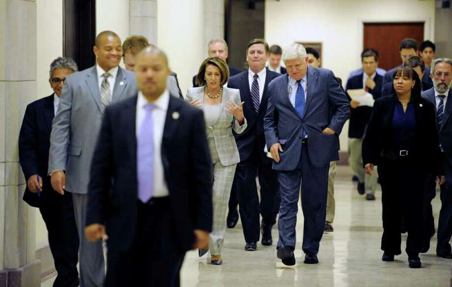 House Democratic Leader Nancy Pelosi, D-Calif., and Rep. John Larsen, D-Conn., are surrounded by staff and security as they walk down a hallway on their way to  news conference about creating jobs, on Capitol Hill, in Washington, Tuesday, Sept. 6, 2011. (AP Photo/Cliff Owen) Photo: Cliff Owen