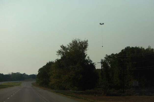 A helicopter helps fight the wildfire with water drops between Smithville and Bastrop on Wednesday, Sept. 7, 2011. Photo: LISA KRANTZ, Lisa Krantz/lkrantz@express-news.net / SAN ANTONIO EXPRESS-NEWS