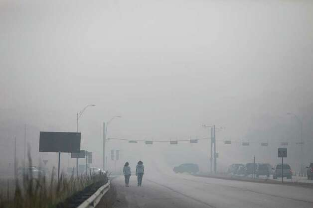 As smoke drifts into the city of Bastrop Wednesday morning, Sami Frye, left, and Suzi Schwark walk west on Hwy 71 past the intersection of Hwy 95 after trying unsuccessfully to check on the Tiger Tote food store and gas station where they are employed east of the intersection which is blocked off in the direction of the store in Bastrop on Sept. 7, 2011. Photo: LISA KRANTZ, Lisa Krantz/lkrantz@express-news.net / SAN ANTONIO EXPRESS-NEWS